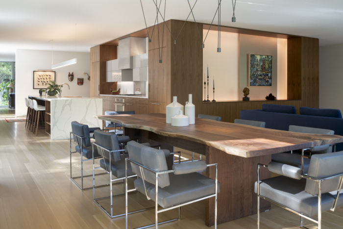 In this modern home located in Highland Park Il., a central volume finished with Walnut veneer contains a kitchen,  laundry, closets, powder room, and living room elevation.  Wheeler Kearns Architect. Image credit Tom Rossiter Photography