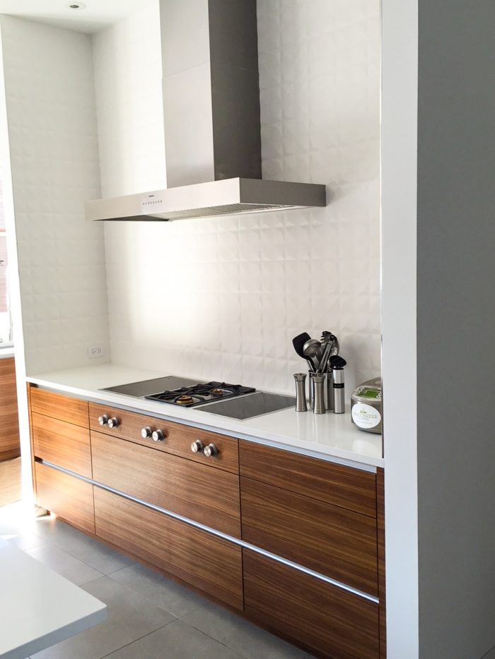 Part of a larger kitchen design, this cook top with deep wide storage drawers is made with solid walnut drawer boxes and walnut veneer drawer fronts. Instead of pulls we used an aluminum finger pull located behind the top of the drawer fronts for a cleaner look.  Architect Mastro & Skylar. Image credit Daniel Baudanza