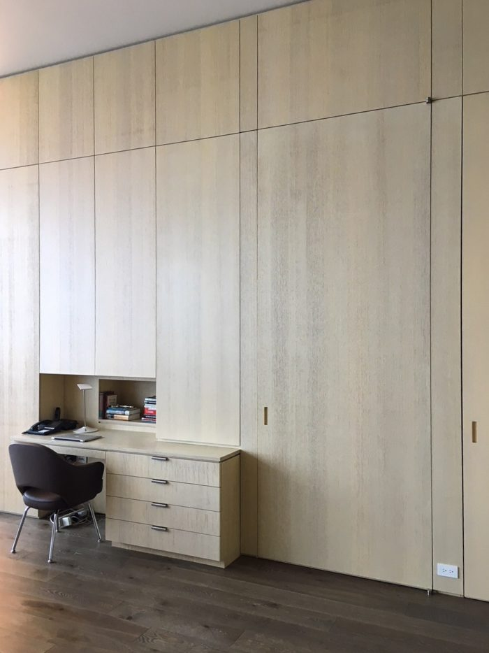 In this project, our millwork was engineered to transition from wall panels that cover existing concrete or drywall  to storage closets and in this case a desk and mini office.  On the right a secondary entry door is concealed with a 10' custom panel door. The veneer is a wire brushed rift white oak with a custom stain.