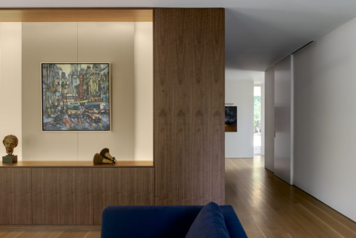 On the living room side of the central volume, a painting hangs on a floating panel which moves to conceal the television.  Wheeler Kearns Architect. Image credit Tom Rossiter Photography