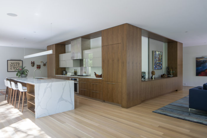 On this side we have a full view of the kitchen with integrated appliances and pantry storage.  The interior cabinet doors are made with a back painted glass.  The back splash is also back painted glass and stainless steel.  We also fabricated the kitchen island which holds a dishwasher and wine fridge. Wheeler Kearns Architect. Image credit Tom Rossiter Photography