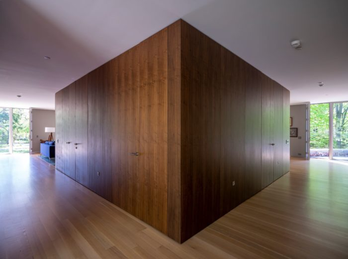 At the rear of the central volume, custom veneer walnut panels conceal a laundry room on the right hand side. The left side has a powder room and storage closet. Wheeler Kearns Architect. Image credit Tom Rossiter Photography